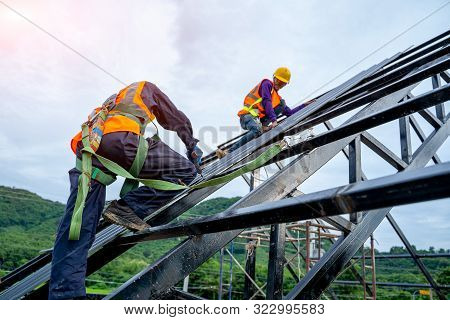 Roofer Worker In Protective Uniform Wear And Gloves, Using Air Or Pneumatic Nail Gun And Installing