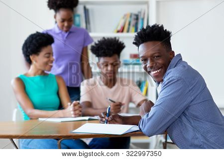 African American Male Student Learning At Desk At School With Teacher And Group Of Students At Class