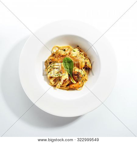 Exquisite serving crispy argentine shrimp, squid with mussels and spaghetti in hot sauce on white restaurant plate isolated. High cuisine restaurent dish with delicious seafood pasta topview