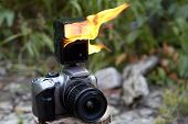 Digital SLR camera with a zoom lens and a burning electronic on-camera flash. Flames on the flash of Digital Single-Lens Reflex Camera against the backdrop of greenery in a forest or park. poster