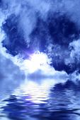 sun among clouds in the blue sky and reflection of the sky in water poster