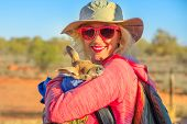 Tourist woman holding kangaroo joey at sunset in Australian outback. Interacting with cute kangaroo orphan for three months. Australian Marsupial in Northern Territory, Central Australia or Red Center poster