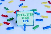 Conceptual hand writing showing De Clutter Your Life. Business photo showcasing remove unnecessary items from untidy or overcrowded places Colored clothespin papers empty reminder white floor office. poster