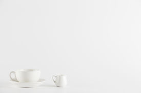 White coffee cup and milk pot on white background