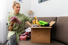 Charity - Woman Sorting Clothes And Put Into The Cardboad Box For Donation