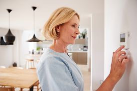 Close Up Of Mature Woman Adjusting Central Heating Temperature At Home On Thermostat