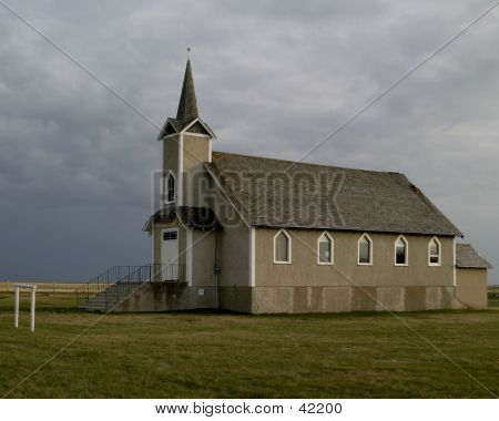 a praire church with rain clouds poster