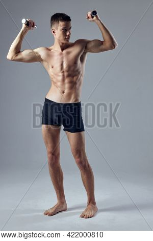 Sporty Man In Black Shorts With Dumbbells In Hands Pumped Up Body Posing