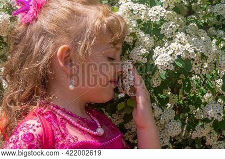 A Little Girl In A Purple Dress Sniffs White Flowers On A Tree.