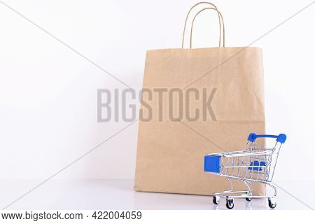Shopping Trolley, Supermarket Trolley, Craft Paper Bag, On A White Background. Copy Space.