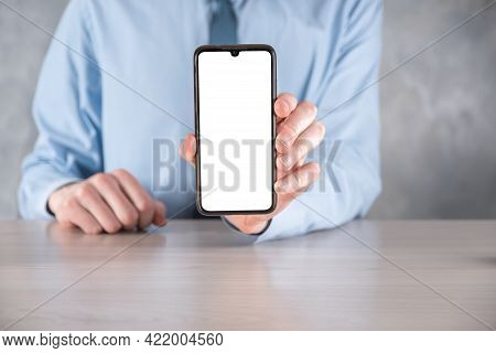 Businessman In A Blue Shirt At Workplace At The Table Holding A Mobile Phone, Smartphone With A Whit