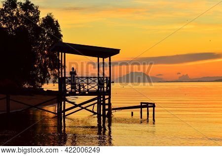 Tropical Beach Background As Summer Landscape With The Fishing Jetty,palm Trees In Sun Rays And Calm