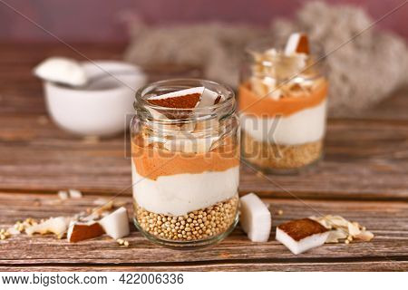 Layered Breakfast Or Dessert With Puffed Quinoa Grains, Yogurt And Coconut Flakes And Pieces In Glas
