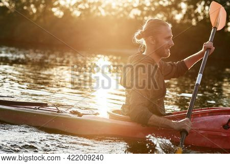 Happy Caucasian Young Guy Looking Cheerful, Holding A Paddle, Kayaking In A Lake Surrounded By Natur