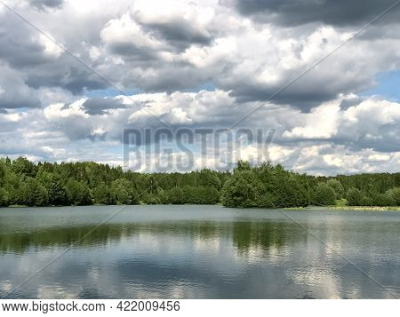 Green Overgrown Lake Shore With Water Reflection On Cloudy Overcast Day With Wave Ripples Against Fo