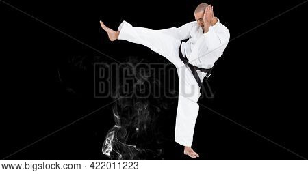 Composition of male martial karate artist with black belt kicking over smoke and copy space. sport and competition concept digitally generated image.