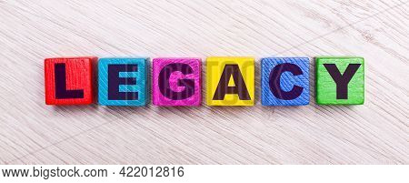 On A Light Wooden Background, Multi-colored Wooden Cubes With The Text Legacy.