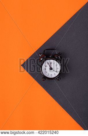 Alarm Clock Showing Five To Twelve On Orange And Black Geometric Background. Time Management Concept