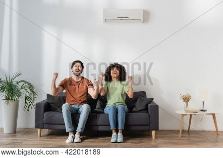 Happy Multiethnic Rejoicing While Sitting On Couch In Modern Living Room, Hvac Concept.