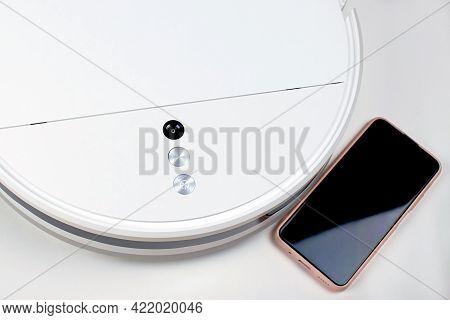 White Robot Vacuum Cleaner And Phone, Close-up. Modern Robot Vacuum Cleaner On A White Background. C