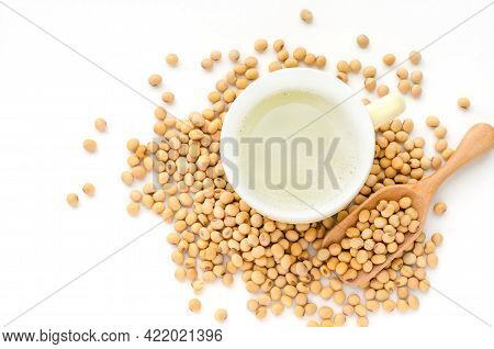 Top View Of Fresh Delicious Homemade Soybean Milk In Soft Yellow Cup With Dry Soybean Seeds On White