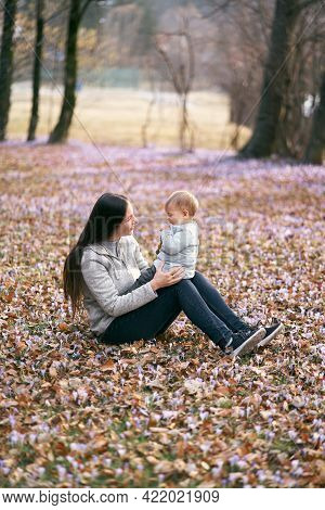 Mom Sits On Fallen Leaves In The Park, Holding The Baby On Her Lap, Sitting With Him Face To Face