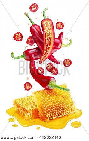Fresh red chilli pepper and sections of chilli pepper floating over honeycombs and honey puddle isolated on white background. File contains clipping path.
