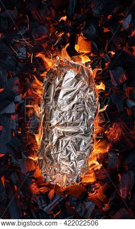 Some food in aluminum foil on grate over hot pieces of coals. Top view.