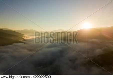 Aerial View Of Vibrant Sunset Over White Dense Foggy Clouds With Distant Dark Silhouettes Of Mountai