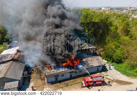 Aerial View Of Firefighters Extinguishing Ruined Building On Fire With Collapsed Roof And Rising Dar