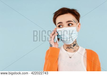 Tattooed Woman In Orange Cardigan And Medical Mask Talking On Smartphone Isolated On Blue.