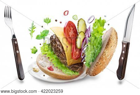 Cheeseburger ingredients and eating utensils hanging in the air. Conceptual picture of fast food. File contains clipping path.