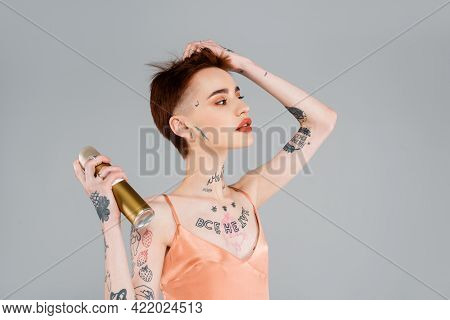Young Tattooed Woman With Red Lips Using Hairspray Isolated On Grey.