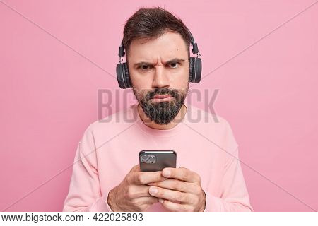 Displeased Serious Bearded Man Wears Stereo Headphones Holds Mobile Phone Downloads Songs To Playlis