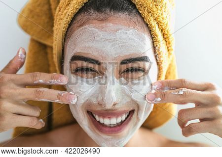 Young Smiling Woman Applying Cream On Face - Happy Girl Having Skin Care Spa Day At Home - Healthy B