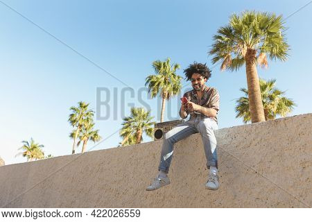Happy Afro Man Having Fun Using Mobile Smartphone While Listening To Music With Vintage Boombox Ster