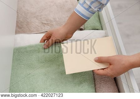 Woman Putting Scented Sachet Into Drawer With Towels, Closeup