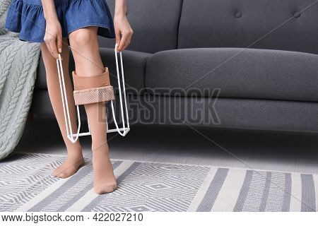 Woman Wearing Compression Tights With Donner On Sofa Indoors, Closeup. Space For Text