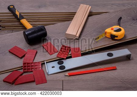 Planks Of Laminate Floor And Equipment Or Tools To Install Them, Hammer, Crowbar, Spacers, Mallet An