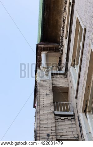 View Looking Up Along Wall Of An Old Brick Apartment Building With Decorative Face Elements, Vertica