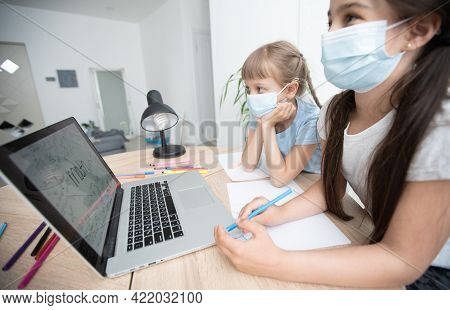 Cute Little Girl Wearing A Medical Mask On Her Face Doing Distance Learning Using A Laptop At Home I