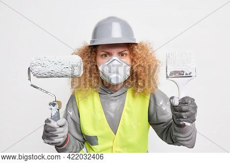 Serious Woman Builder Involved In House Remodeling Holds Paint Brush And Roller Wears Protective Hel