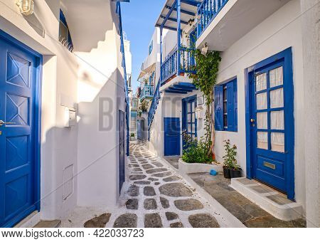 Beautiful Traditional Narrow Alleyways Of Greek Island Towns. White Houses, Flower Pots, Blue Balcon
