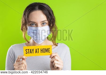 Young Woman In Medical Mask Holding Card With Stay Home Lettering On Isolated On Green