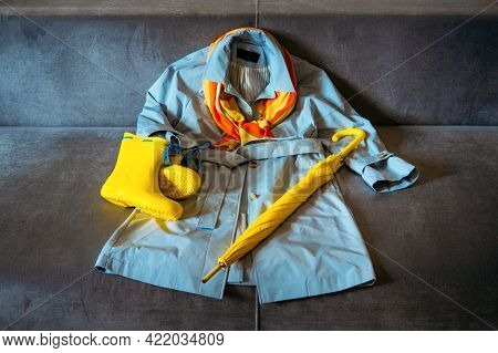 Rainy Mood, Outfit For Rainy Day. Blue Raincoat, Yellow Rubber Boots And Umbrella On A Gray Sofa. Co