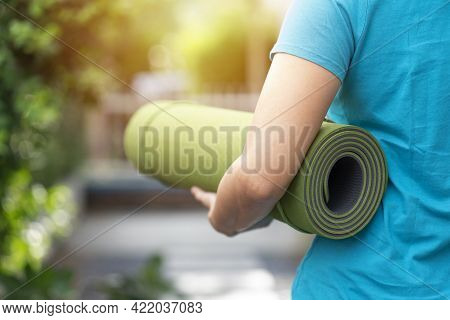 Young Woman Holding A Yoga Mat In Exercise Class For A Sport And Healthy Concept