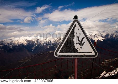Caution Sign Might Drop From Cliff. Warning. The Danger Of Falling Warning Sign On A Steep Mountain