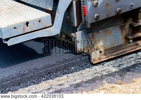 Asphalt Paver On The Road While Laying Asphalt, Part Of The Car Close Up. Road Repair. Laying A New