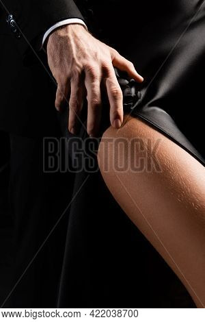Close Up View Of Male Hand Passionately Touching Hip Of Woman In Silk Dress Isolated On Black.