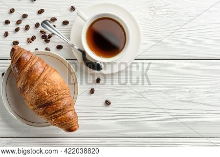 A Cup Of Coffee And A Croissant On A White Table With Copy Space. Flat Lay Composition With Coffee A